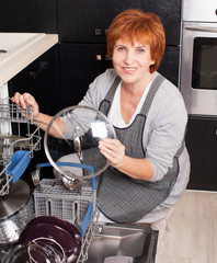 Woman folding the dishes in the dishwasher