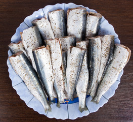 Sprats with salt and pepper ready for cooking on a plate
