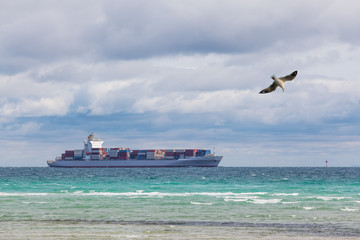 Big cargo ship filled with containers sailing across Mornington