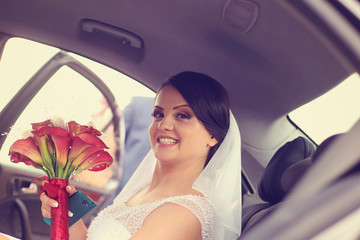 Beautiful bride holding a white and red calla lily