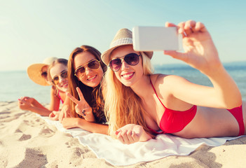 group of smiling women with smartphone on beach