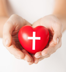 female hands holding heart with cross symbol