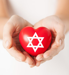 female hands holding heart with star of david