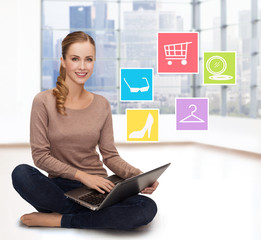smiling woman with laptop shopping online at home
