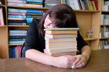 Tired student girl sleeping on the books in the library