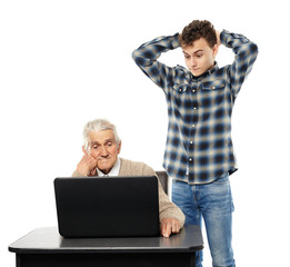 Teen with his granddad at laptop