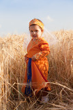 little girl in a national Armenian dress to stand in  field