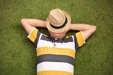 Senior gentleman lying in a field on green grass