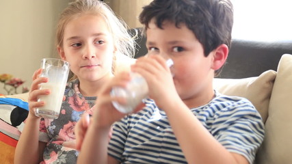 Happy little boy and girl drinking a glass of milk