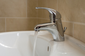 Bathroom sink tap with running water