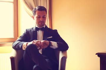 Elegant young fashion man in a hotel room