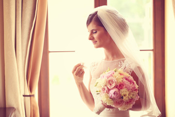 Emotional bride in her wedding day holding peonies bouquet