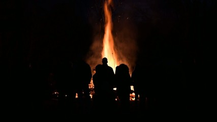 Footage of a large bonfire at night with silhouetted crowd