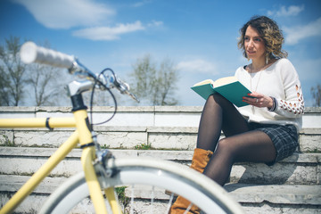 Young woman enjoying a book on her bicycle in grass in city park