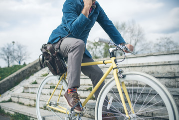 Hipster man with bicycle usingmobile cell phone