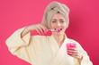 Frau im Bademantel putzt sich die Zähne