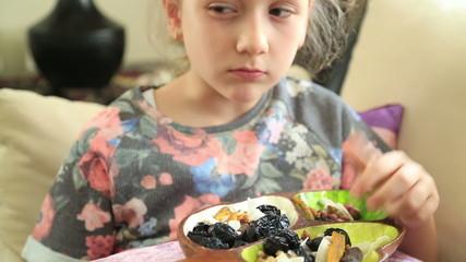 Little girl eating dried fruit