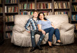 pregnant woman and husband posing on couch at living room