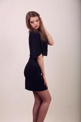 Portrait of beautiful brunette woman in black dress. Fashion pho
