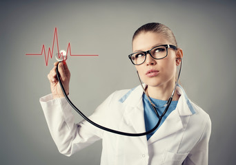 Young female cardiologist with stethoscope and heart cardiogram