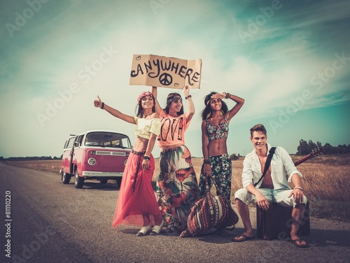 Multinational hippie hitchhikers on a road - 81110220