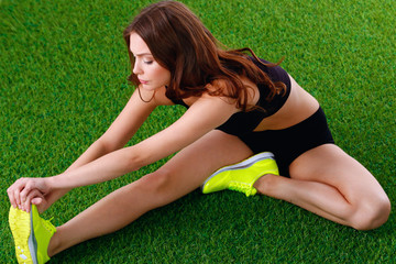 Woman doing stretching exercises on the green grass