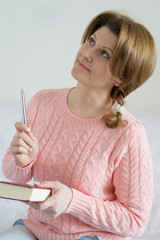 Positive woman with a notebook and pen in hand