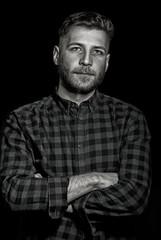 Young man on dark background, dramatical lowkey portrait