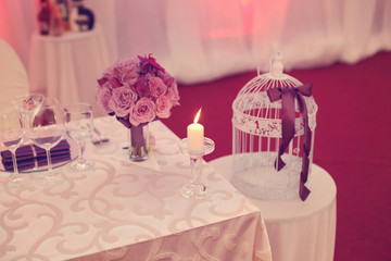 Candle on table with flowers and birdcage