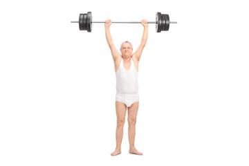 Semi-dressed senior lifting a heavy barbell