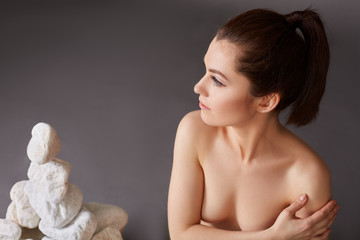 Pensive nude woman and stones on background