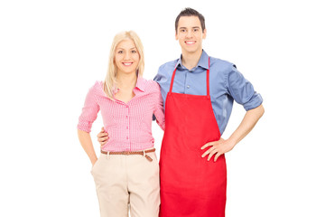 Man with a red apron posing with his blond girlfriend