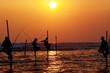 Leinwanddruck Bild - Silhouettes of the traditional stilt fishermen at the sunset nea