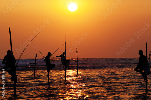 Leinwanddruck Bild Silhouettes of the traditional stilt fishermen at the sunset nea