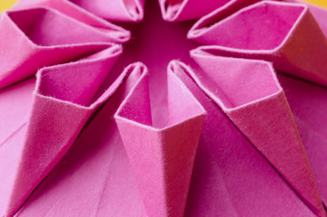 abstract closeup of one side of a pink paper origami flower