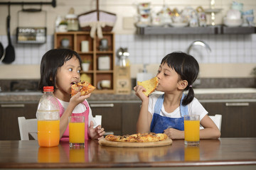 Two Little Girls Eating Pizza