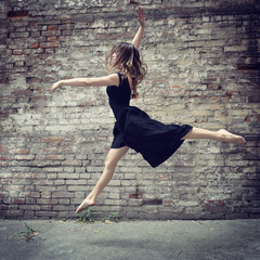Attractive teen girl dancing outdoor against grunge brics wall.