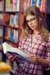 Portrait of teenage student reading book in library class