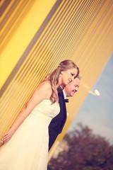 Bride and groom near yellow wall