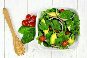 Salad with greens, avocado, tomatoes, onions on white wood table