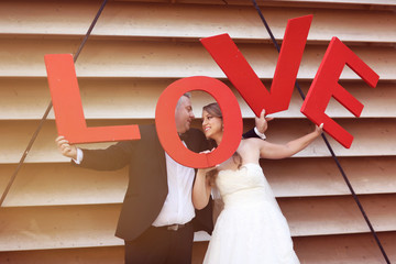 Bride and groom holding big red LOVE letters
