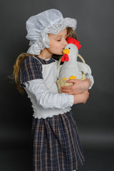 Girl in dress rustic vintage holds a chicken and kisses