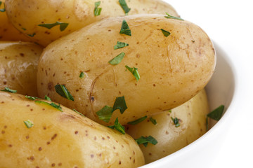 Shiny boiled small potatoes with parsley in bowl. Detail.