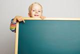 Fototapety Kind zeigt auf leere grüne Tafel