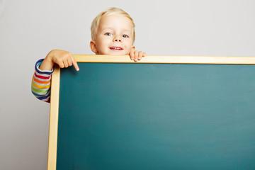 Kind zeigt auf leere grüne Tafel