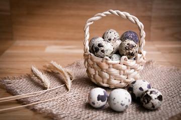 Bird eggs in wicker basket on wooden background