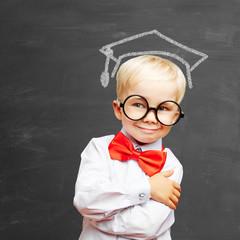 Kind vor Tafel mit Doktorhut als Symbol