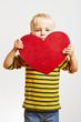 Lächelnder Junge hält rotes Herz
