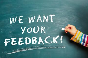 Hand schreibt We want your Feedback