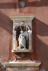 Statue on a house facade in Venice